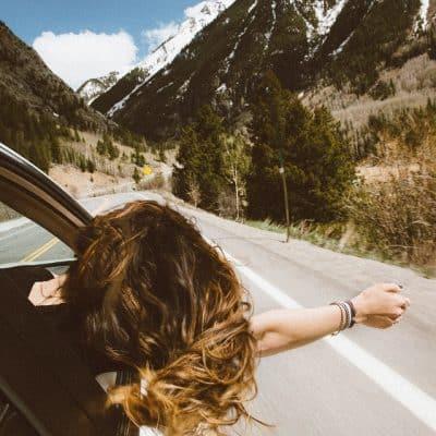Femme passant la tête par la fenêtre d'une voiture