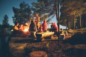 Vacanciers autour d'un feu de camp la nuit dans un camping