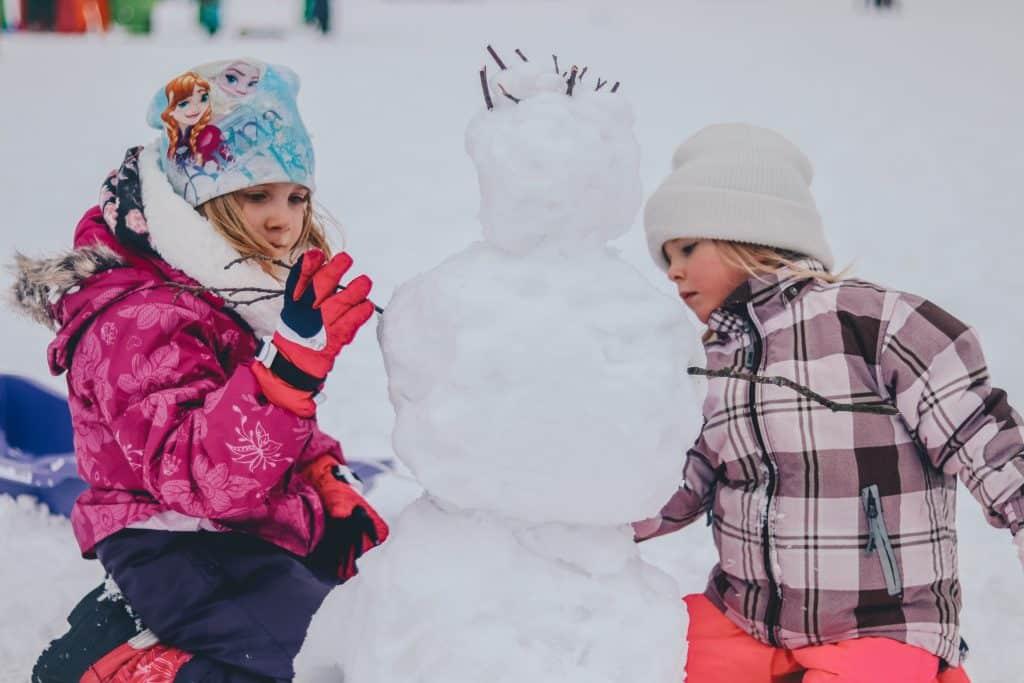 deux enfants qui construisent un bonhomme de neige