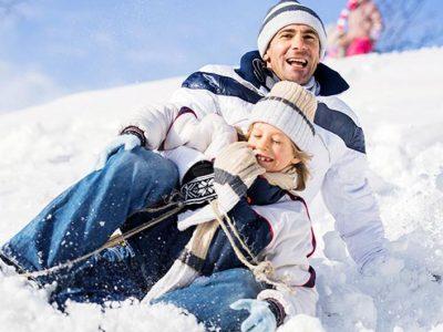père et fils faisant de la luge dans la neige
