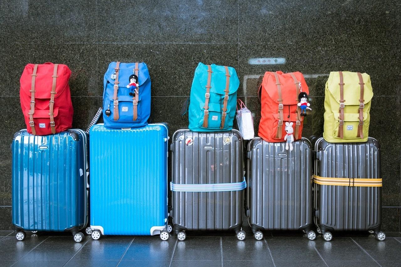 Plusieurs valises côte à côte sur lesquelles sont empilées des sacs à dos de toutes les couleurs