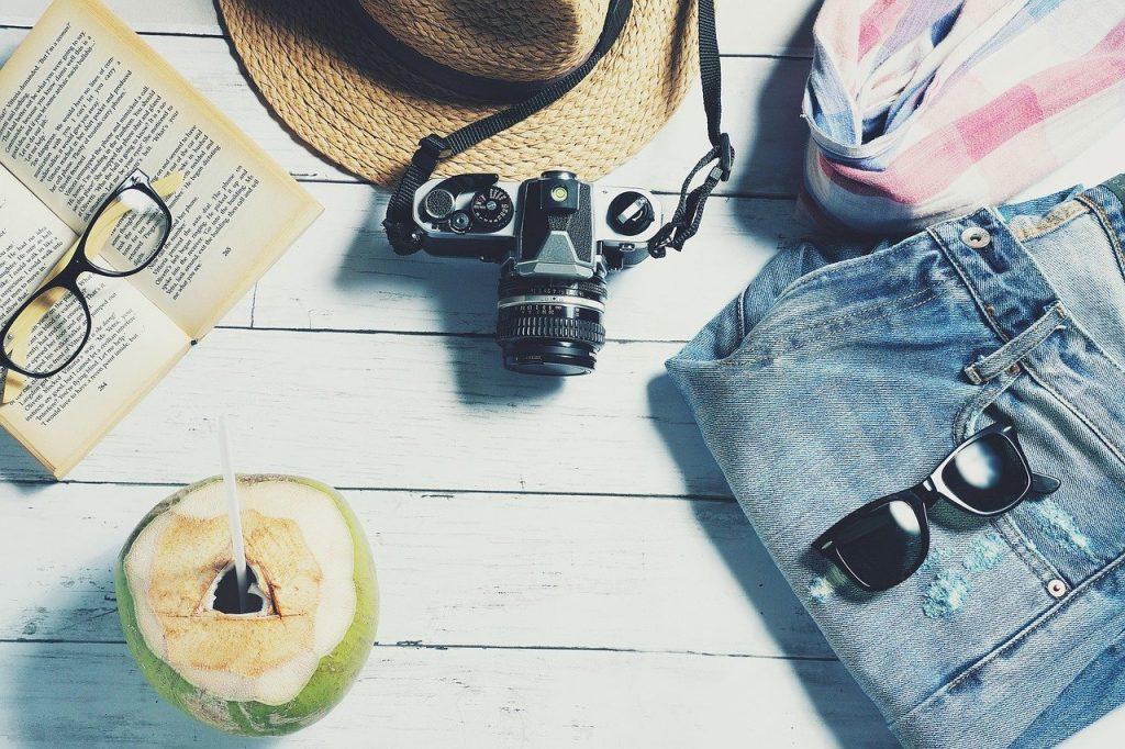noix de coco, livre, appareil photo, chapeau, lunettes de soleil et short posés sur des planches